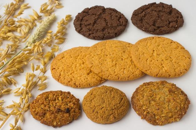 Различные виды печенья и овсяных веток на белом