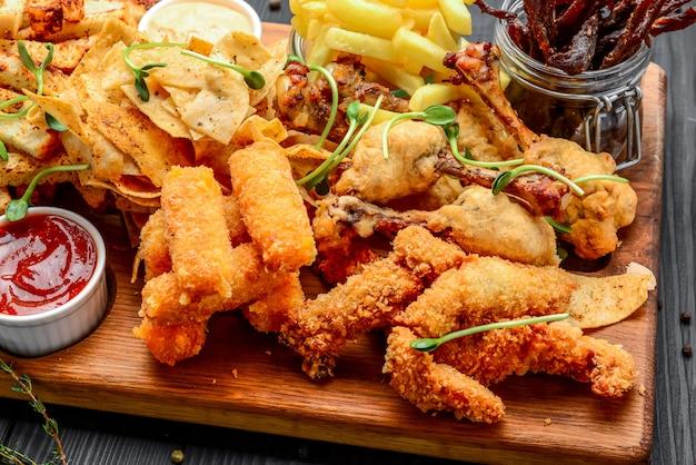 さまざまな種類の揚げスナック:チキン、チーズ、オニオン、イカのリング、エビ、キノコ