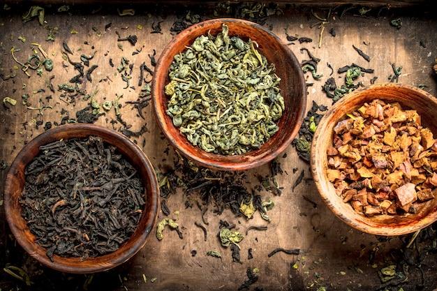 Разные виды ароматного чая в мисках. на деревенском фоне.