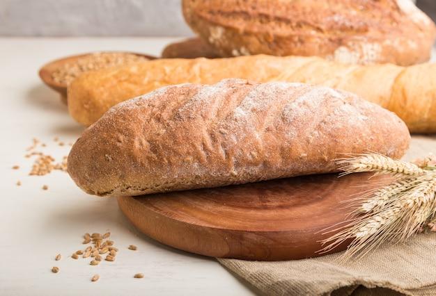 白い木製のテーブルで焼きたてのパンの種類。側面図、クローズアップ。