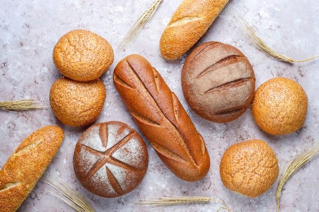 Различные виды свежего хлеба в качестве фона, вид сверху
