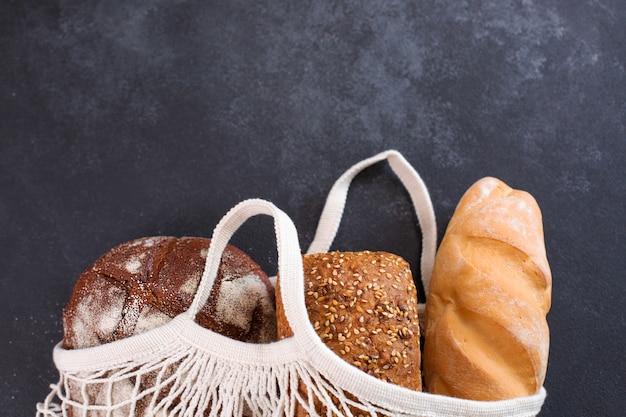 흰색 메쉬 토트백에 담긴 다양한 종류의 신선한 빵