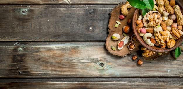 葉の入ったボウルにさまざまな種類のナッツ。木製の背景に。