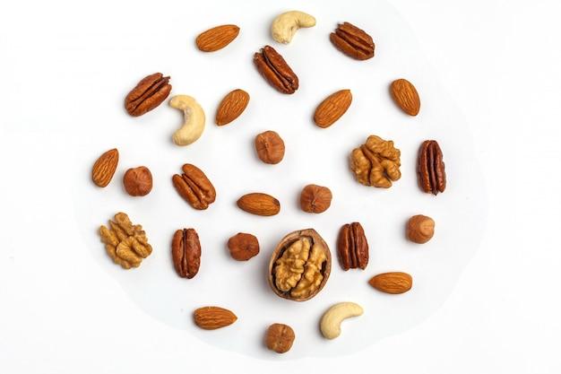 白で隔離され、円の形をしたナッツの種類