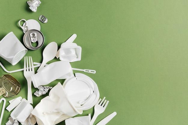 Различные виды пластикового мусора на зеленом фоне. концепция переработки пластика и экологии. плоская планировка, вид сверху