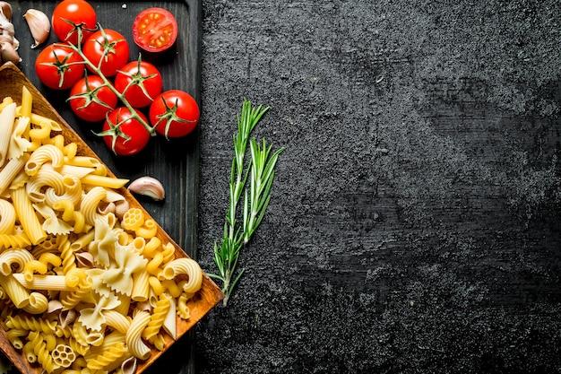 Различные виды сырой пасты на тарелке с помидорами, чесноком и розмарином. на черном деревенском фоне