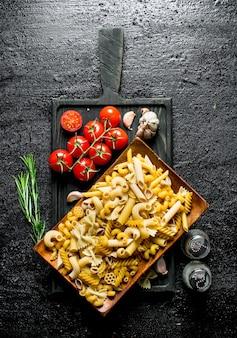 Различные виды сырой пасты на тарелке с помидорами, чесноком и розмарином.