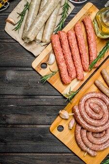 Различные виды сырых колбас на деревянной доске со специями. на деревенском столе.