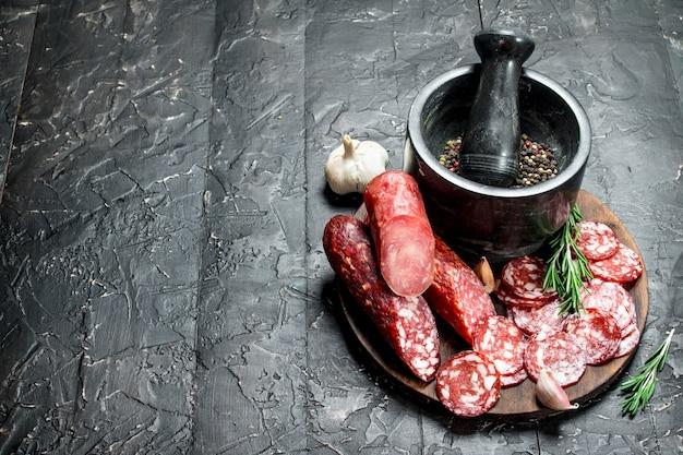 黒の素朴なテーブルにスパイスとハーブを添えたさまざまな種類のサラミ。