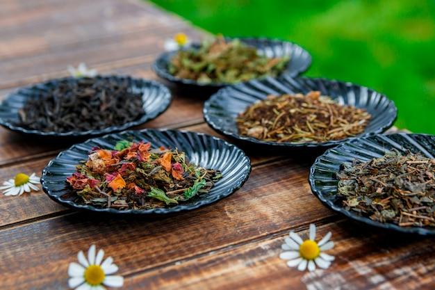 庭と自然の背景にカモミールの花を持つ木製テーブルの黒い皿にお茶の種類。乾燥茶の品揃え。お茶のコンセプト。茶葉。閉じる