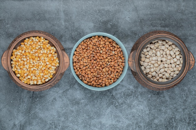 さまざまな鍋にあるさまざまな種類の未調理の豆とトウモロコシ。