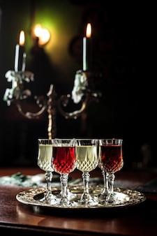 Разные виды вермута в маленьких рюмках на серебряном подносе, красивый старинный подсвечник со свечами