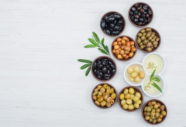 Different kinds of olives and olive oil in a clay and white bowls with olive leaves flat lay on white wood