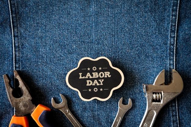 レンチ、便利なツールと青のジーンズの背景に木製のタグにさまざまな種類。