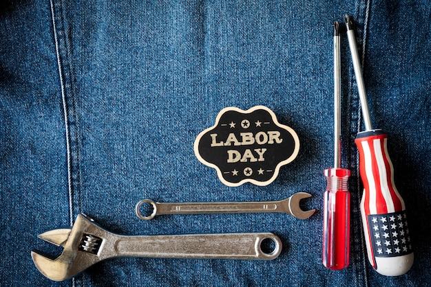 レンチ、便利なツール、青いジーンズの背景に木製のタグでさまざまな種類。
