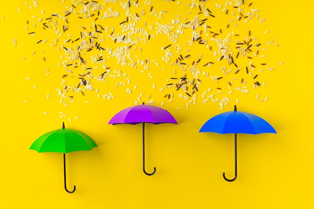 Different kinds of rice grains pouring on three toy umbrellas on yellow table. artistic concept of spring rain