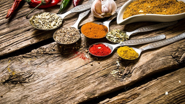 Different kinds of spices in spoons. on a wooden background.