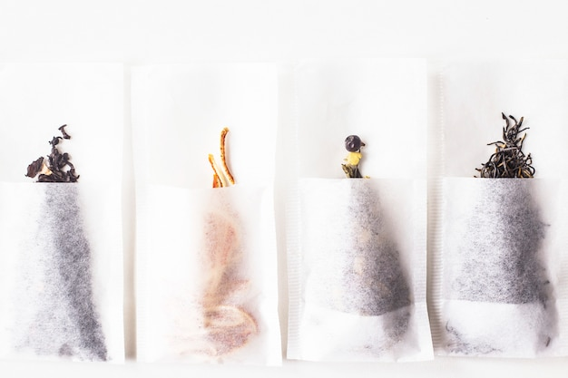 Different kinds of tea in disposable filter packs lined up in a row on a white background. top view, flat lay