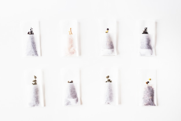Different kinds of tea in disposable filter packs lined up on a white background. top view, flat lay
