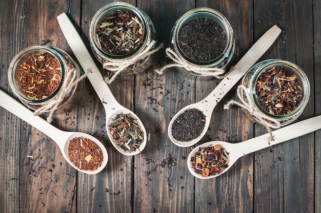 Different kinds of tea in jar and wooden spoons on wood table.