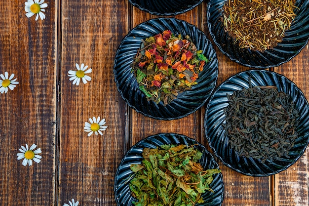 Different kinds of tea on plates on wooden  with flowers of chamomile . assortment of dry tea. tea . tea leaves. top view. copyspace, frame.