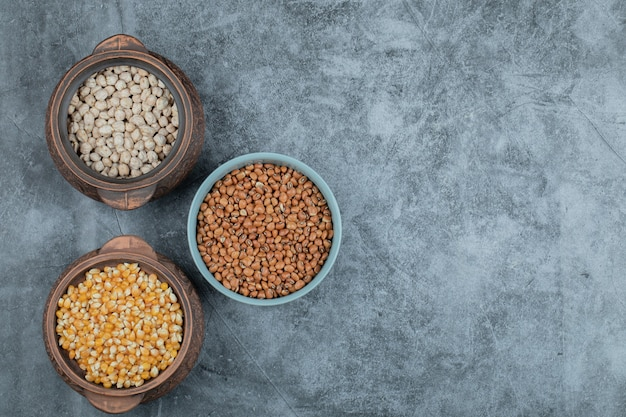 Different kinds of uncooked beans and corns in various pots.