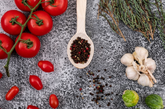 Different kinds of vegetable with pepper on wood spoon on stone background