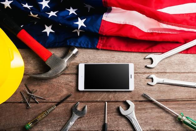 Различные виды гаечных ключей, американский флаг и пустой экран смартфона