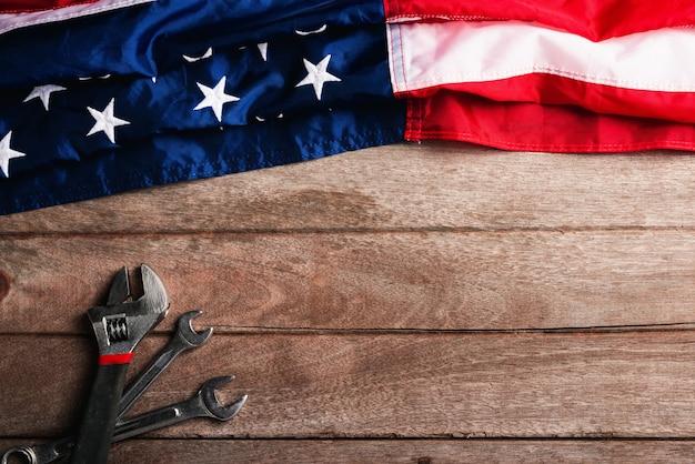 나무 테이블 배경에 미국 국기와 다른 종류의 렌치