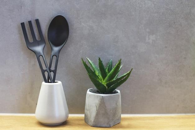 Различные кухонные инструменты для приготовления пищи на серой бетонной стене кухонная посуда с пластиковым материалом