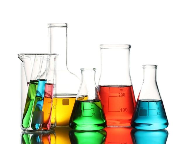 色の液体と白で隔離される反射の異なる実験用ガラス製品