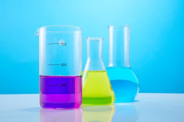 Различные лабораторные изделия из стекла с цветной жидкостью на синей стене. пробирки с разноцветными жидкостями для лабораторных химических исследований.