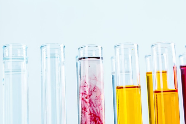 Different laboratory glassware with colored liquids close up
