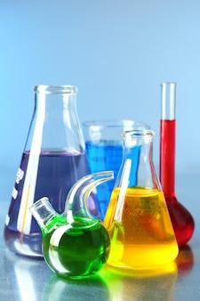 Различная лабораторная посуда с разноцветной жидкостью на цветной поверхности
