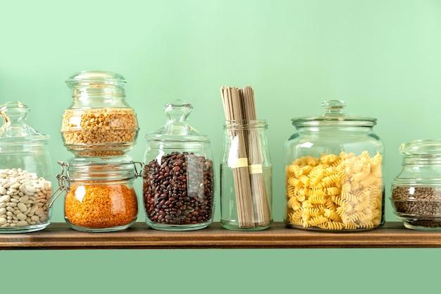 ガラスの瓶の中のさまざまなマメ科植物:ひよこ豆、パスタ、豆、エンドウ豆、緑の背景のレンズ豆。ゼロウェイストストレージ、プラスチックフリー。