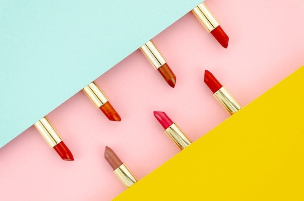 Different lipsticks on colorful background