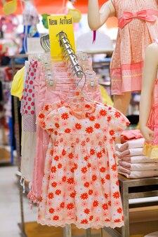 店のハンガーに別の小さな女の子のドレス