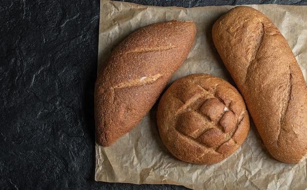Diverse pagnotte di pane su sfondo nero.