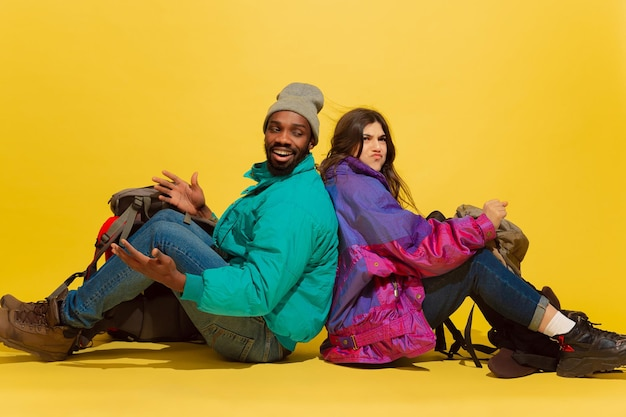 상황의 다른 모습. 노란색 스튜디오 배경에 고립 된 가방과 쾌활 한 젊은 관광객 부부의 초상화.