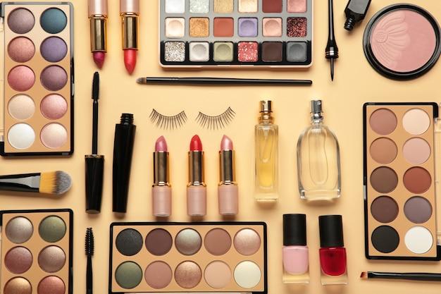 Различные роскошные косметические продукты на бежевом фоне, плоская планировка. вид сверху