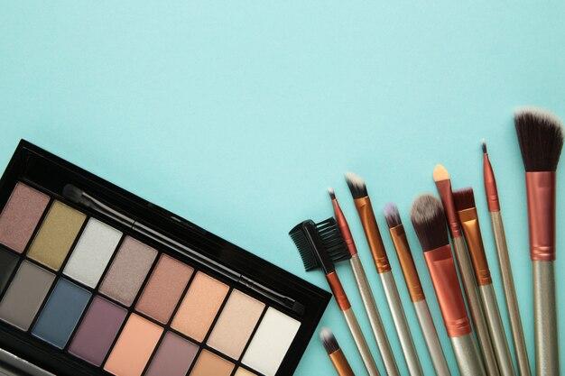 Различные роскошные косметические продукты на синем фоне, плоская планировка. вид сверху