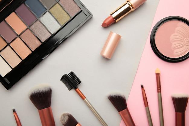 Различные роскошные косметические продукты на красочном фоне, плоская планировка. вид сверху