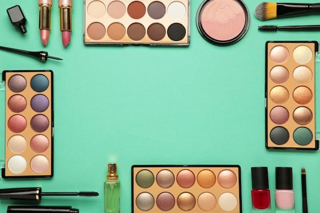 Различные роскошные косметические продукты на мятном фоне, плоская планировка. вид сверху