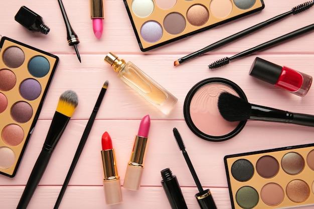 Различные роскошные косметические продукты на розовом фоне, плоская планировка. вид сверху