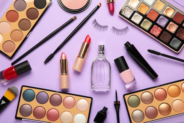 Различные роскошные косметические продукты на фиолетовом фоне, плоская планировка. вид сверху