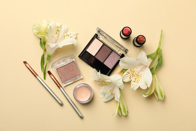 別の化粧品とベージュ色の背景の花。女性のアクセサリー
