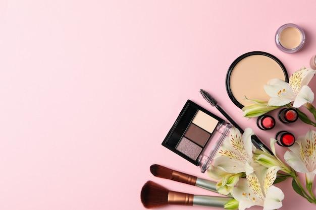 別の化粧品とピンクの背景の花。女性のアクセサリー
