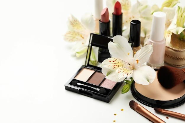 別の化粧品と白い背景の上の花。女性のアクセサリー