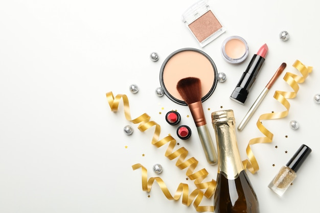 Different makeup cosmetics and champagne on white background