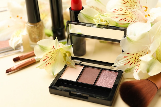 Different makeup cosmetics and flowers on beige background